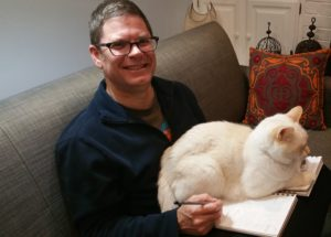 David Borden trying to work on a comic book but his cat is sitting on it