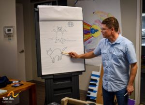 David Borden standing at pad demonstrating how to draw a dancing cat in a cartooning class.