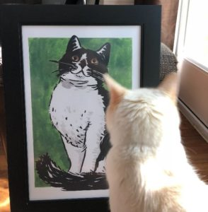Charlie Cat admiring a cat poster by Ruby Borden