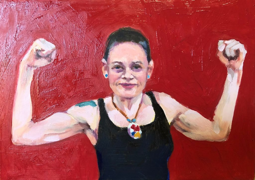 portrait of Tanya, a young woman holding her arms up to show her muscles.